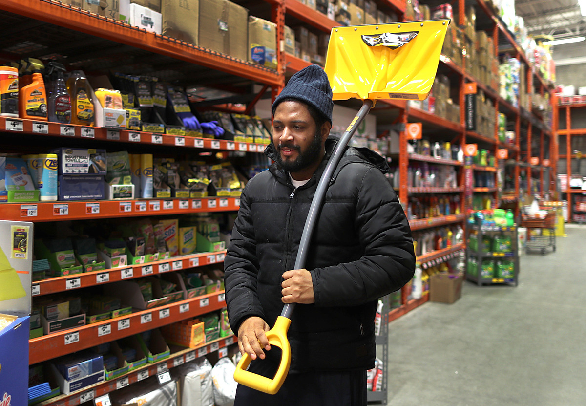 A man carries a snow shovel to the register at Home Depot.