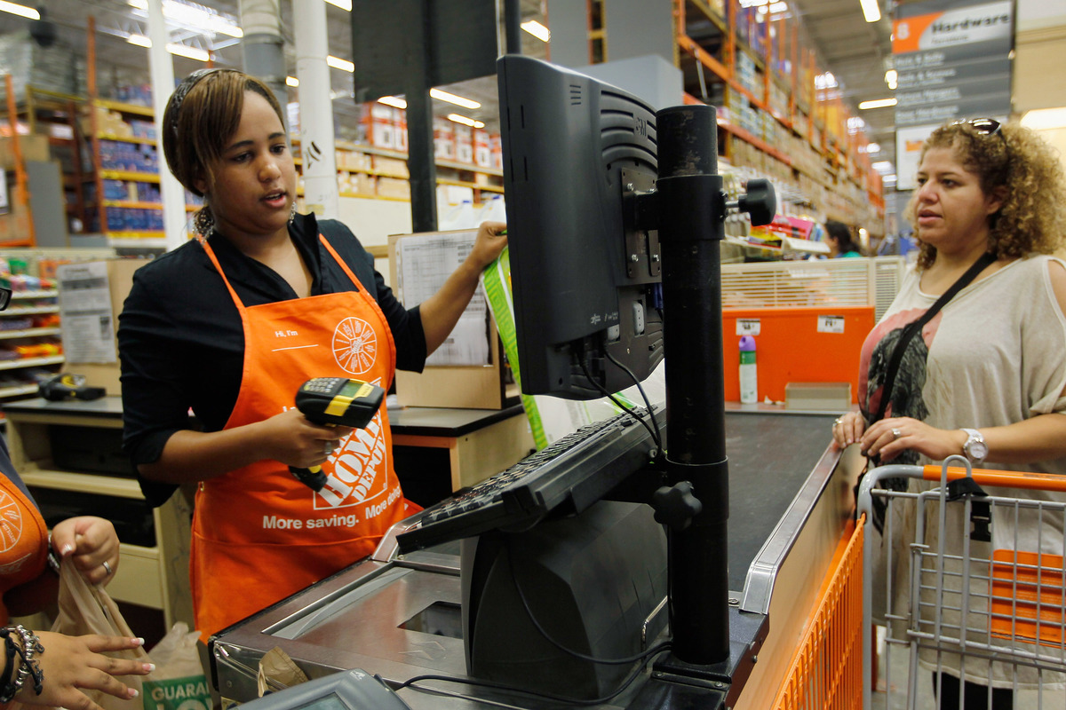 An employee scans a customer's items at Home Depot.