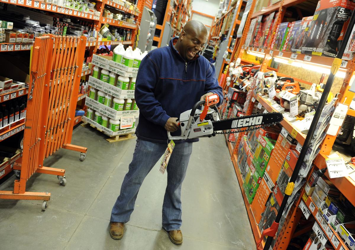 Chris Grundy, host of a popular tool show, shows off a chainsaw in Home Depot.
