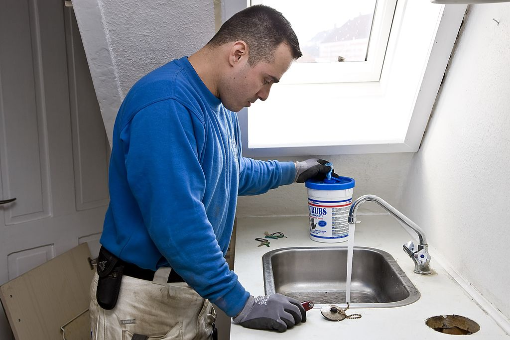 A plumber looks down the sink while running water.