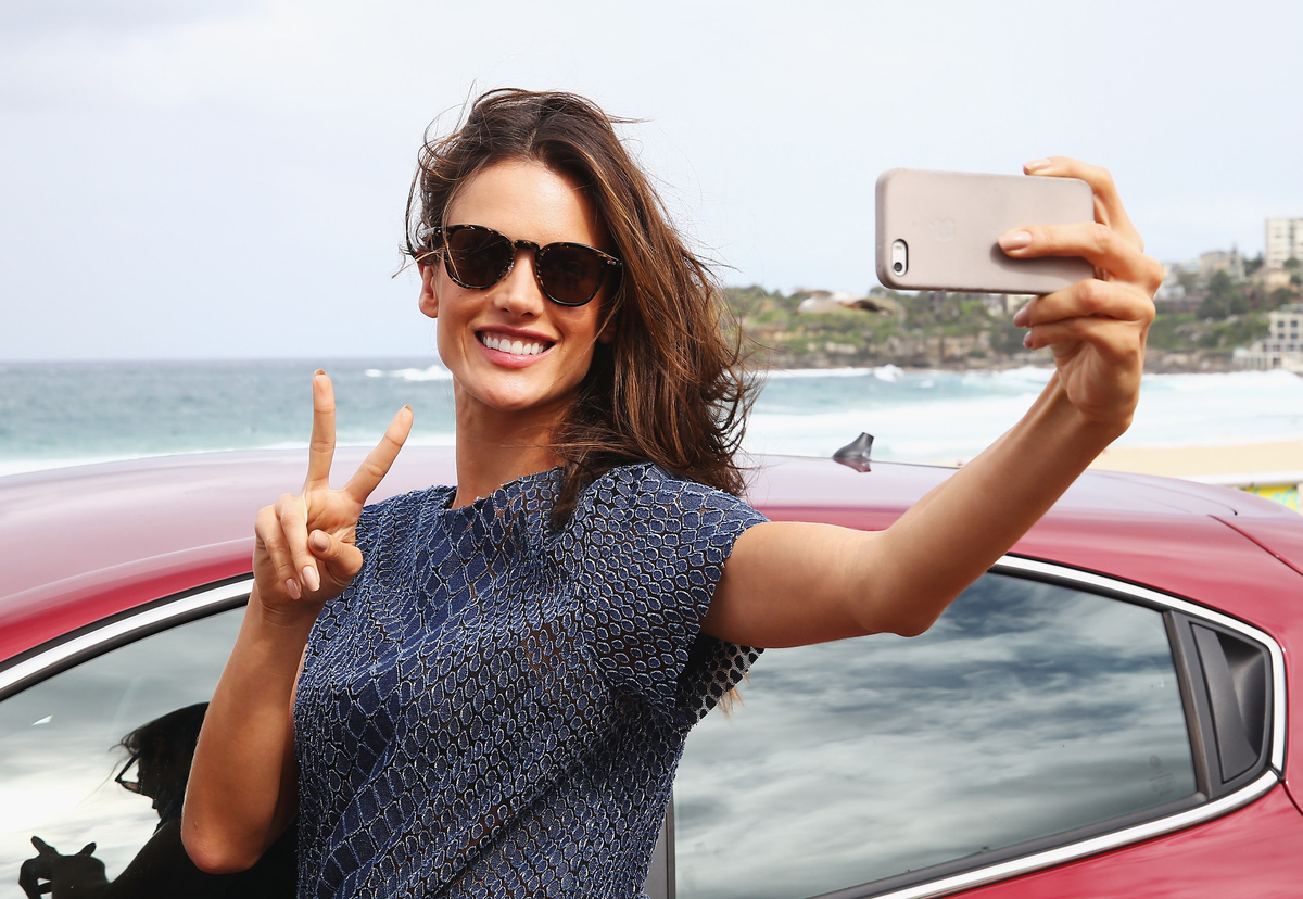 A model takes a selfie in front of a car by the beach.