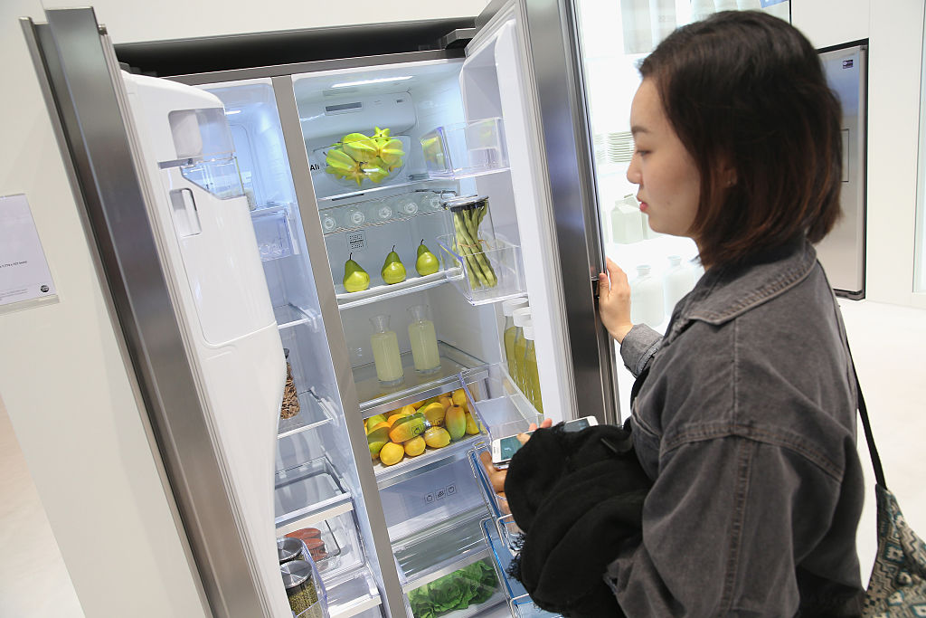 A woman looks inside a spotless fridge.