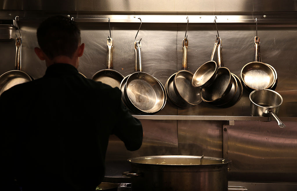 Pots and pans dangle on hooks in front of a chef.