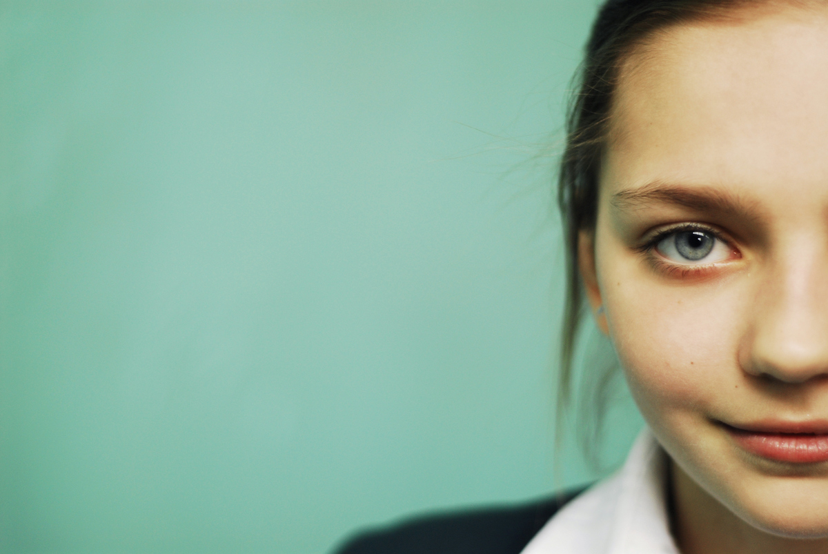 Half of a blue-eyed teenager girl's face is seen.