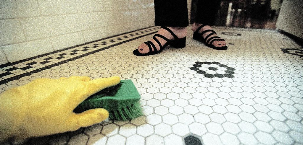 A woman stands before someone scrubbing the tile floor.