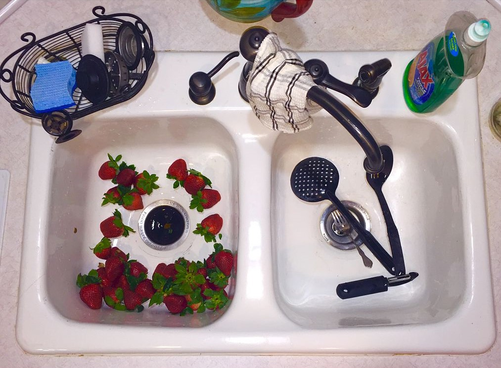 A white sink is full of strawberries.