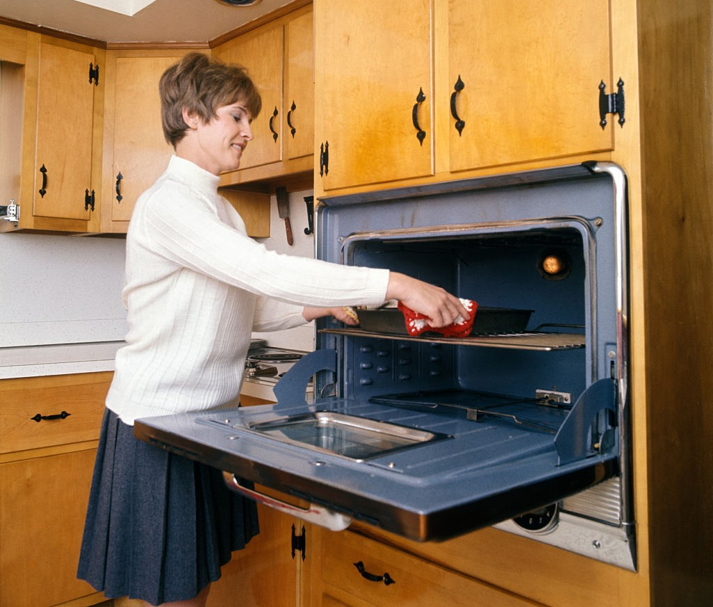 A woman places something into a clean oven.