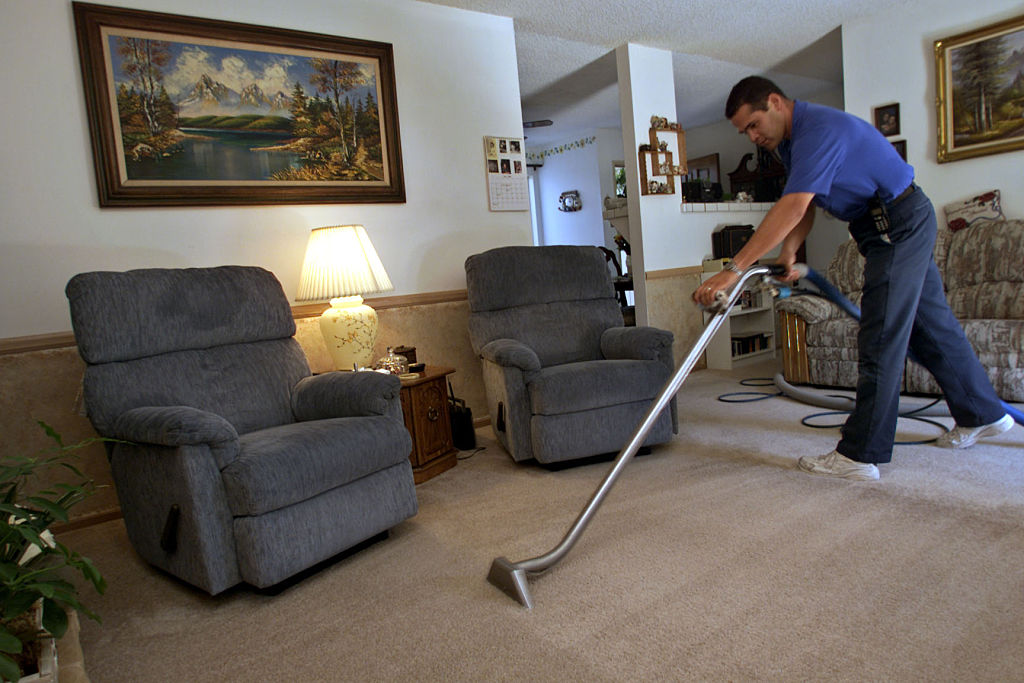 A man cleans carpet in a living room.