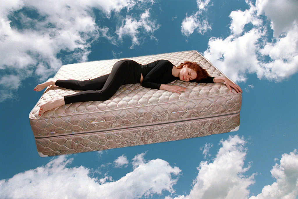 A woman sleeps on a mattress in the sky.