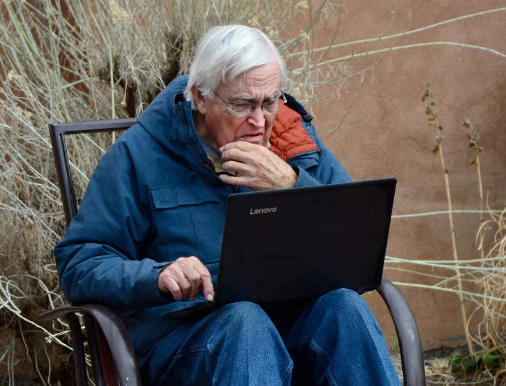 An old man looks hard at his open laptop.