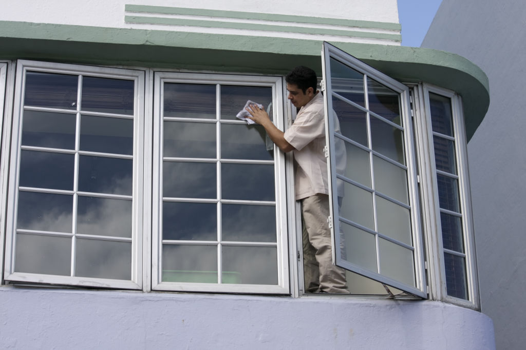 A man leans out a window to clean the glass.
