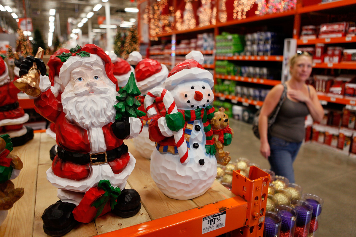 A woman walks by Christmas merchandise offered for sale at a Home Depot.