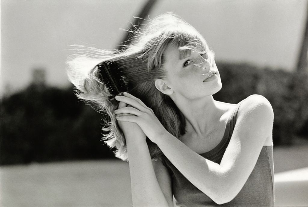 A model brushes her hair.