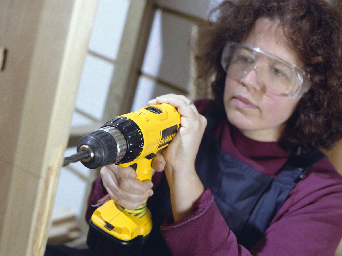 A woman uses a power drill on a wooden plank.