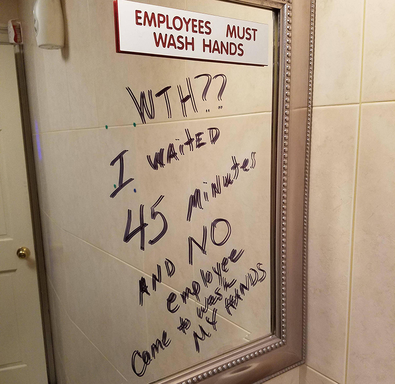A bathroom mirror reads