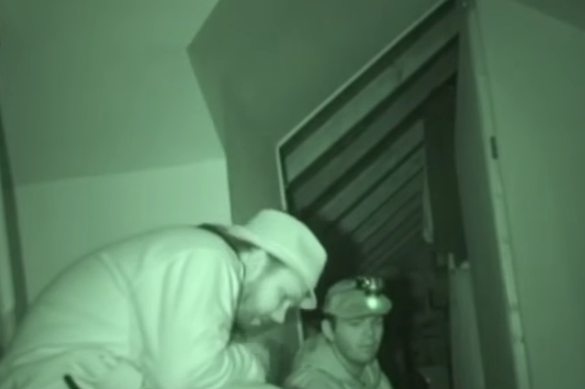 Mike and his partner listen in the dark to a ghost voice.