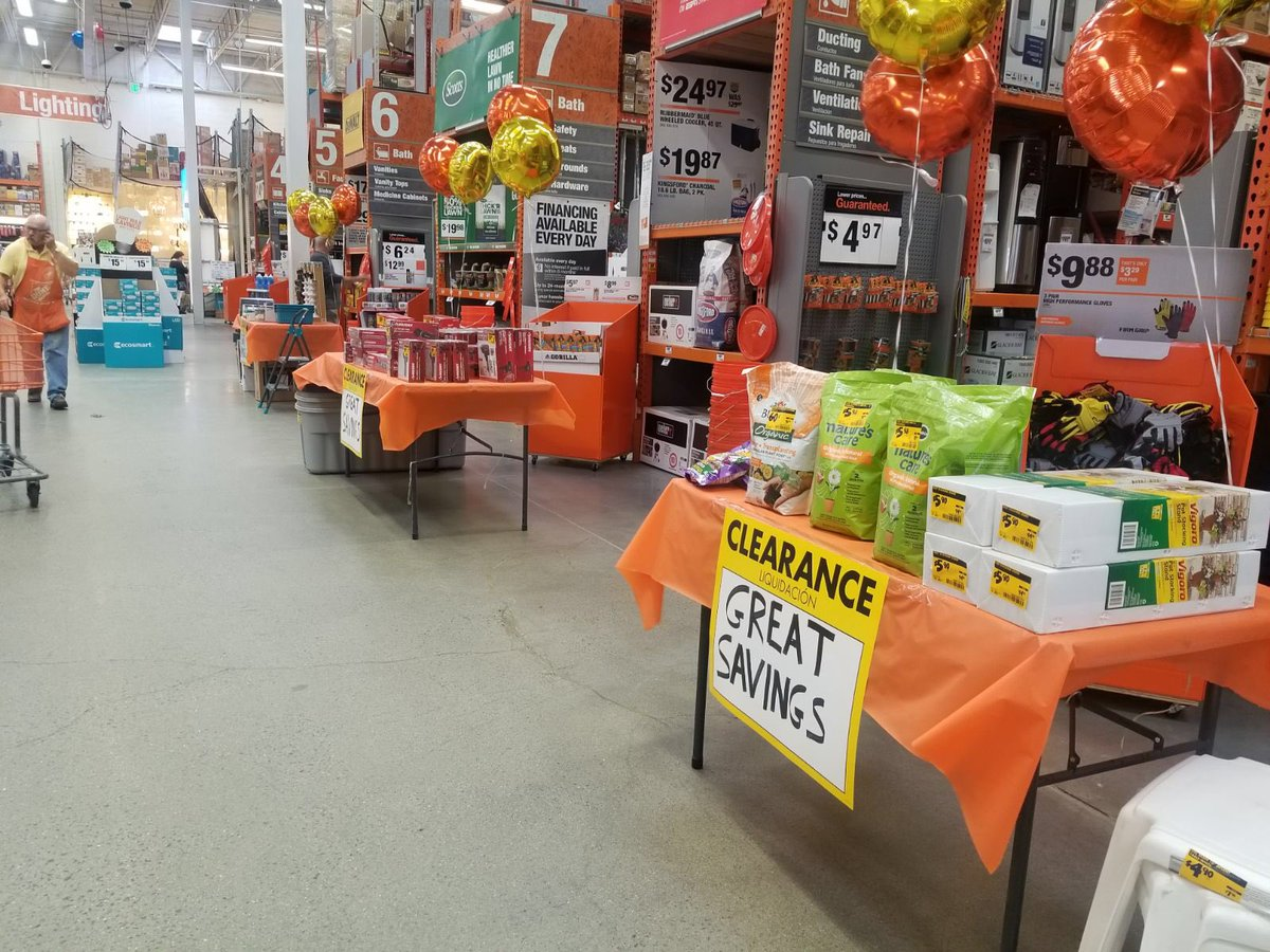 Tables at the ends of aisles in Home Depot offer sales.