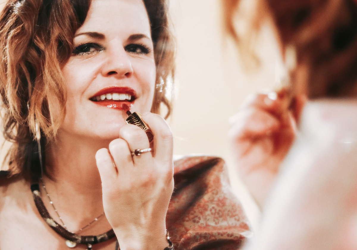 A woman applies red lipstick while looking in a mirror.