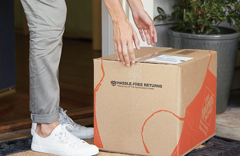 A person picks up a Home Depot box that was delivered to their doorstep.