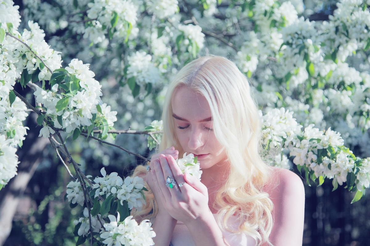 A teenager with glowing skin smells spring blossom flowers.