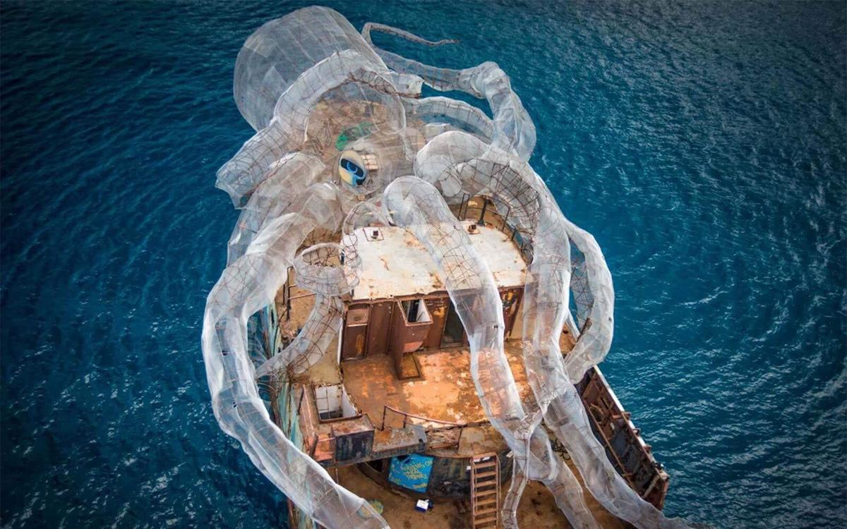 An artificial reef shaped like a kraken wraps around an old boat, ready to be submerged underwater.