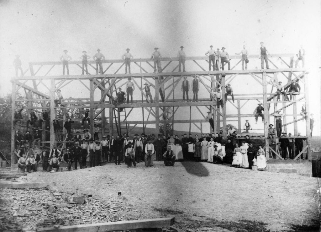 Group of barn raising participants posed in front of the structure in progress
