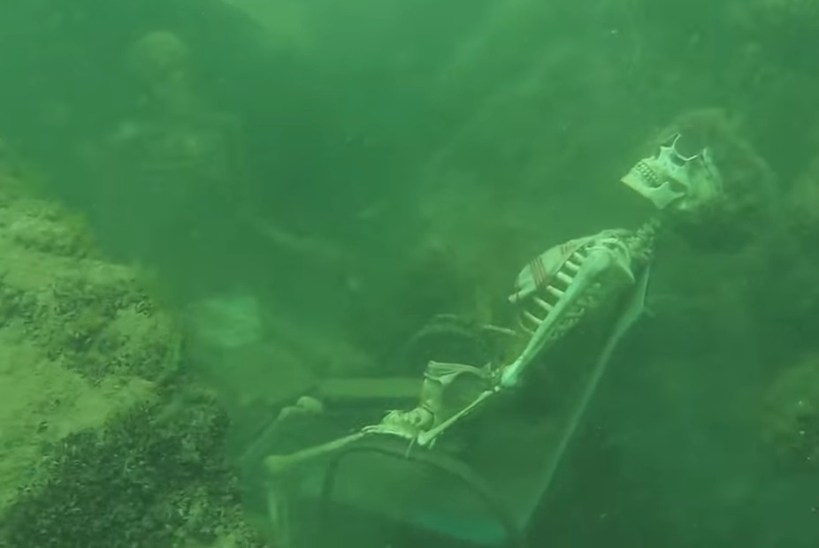 A fake skeleton wearing a wig and glasses is tied to a chair underwater.