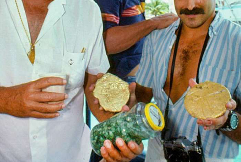 A man carries emeralds found underwater in an old salsa container.
