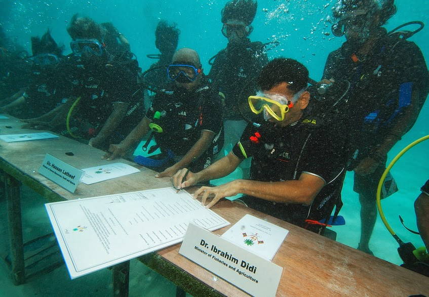 Government officials carry out a meeting underwater.