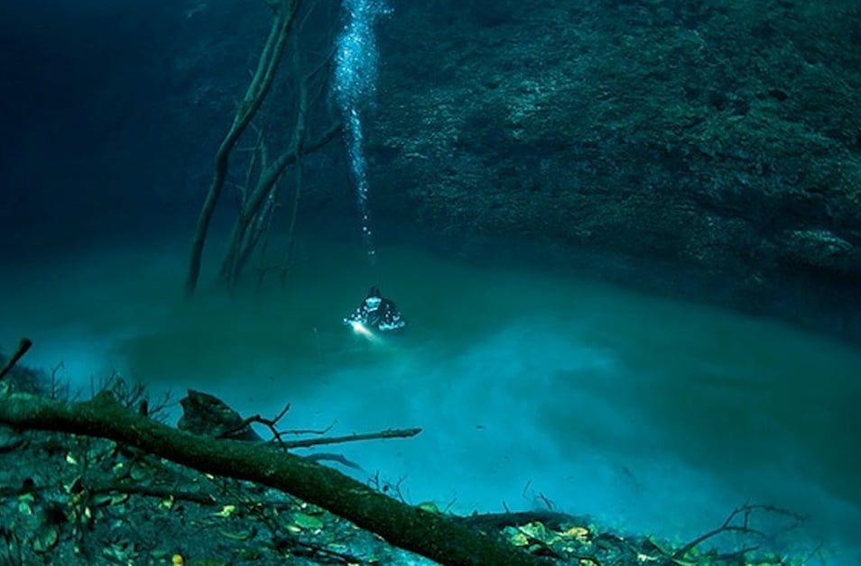 A diver sits in an underwater river in Mexico.