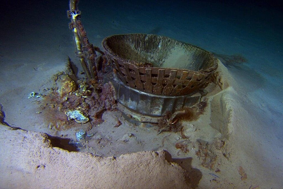An F-1 engine, part of a sunken Saturn V rocket, lies at the bottom of the ocean.