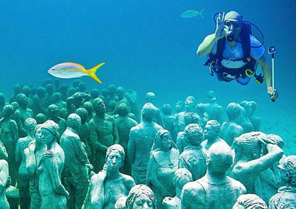 A diver swims above the statues of Cancun Underwater Museum.