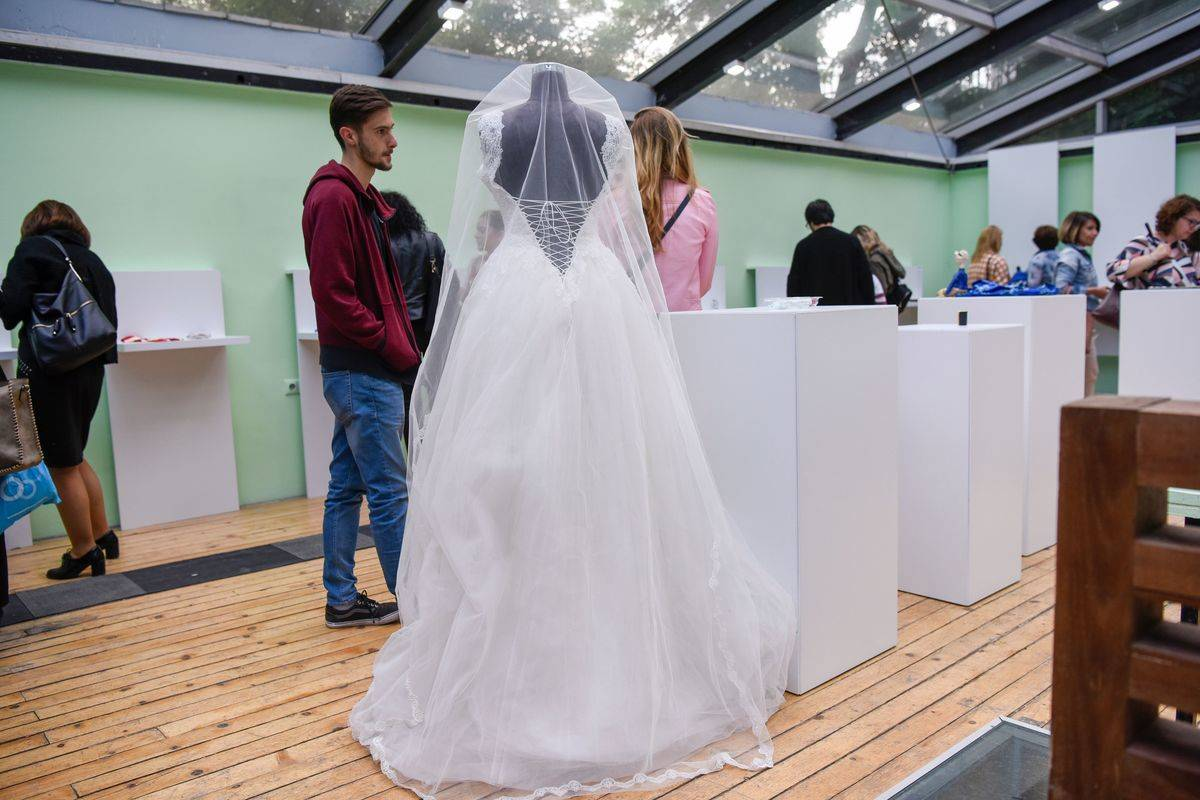 Visitors look at a wedding dress presented during the opening of the Museum of Broken Relationships.