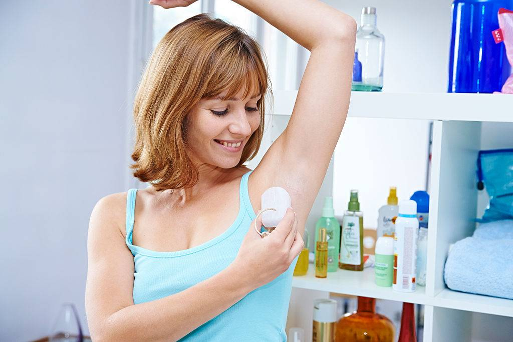 a woman putting on deodorant