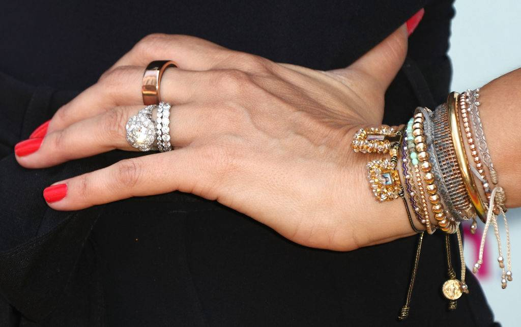 a close up of a woman wearing diamond rings and bracelets