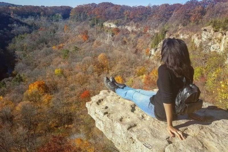 A woman sits on the edge of a rock overlooking a valley of trees.