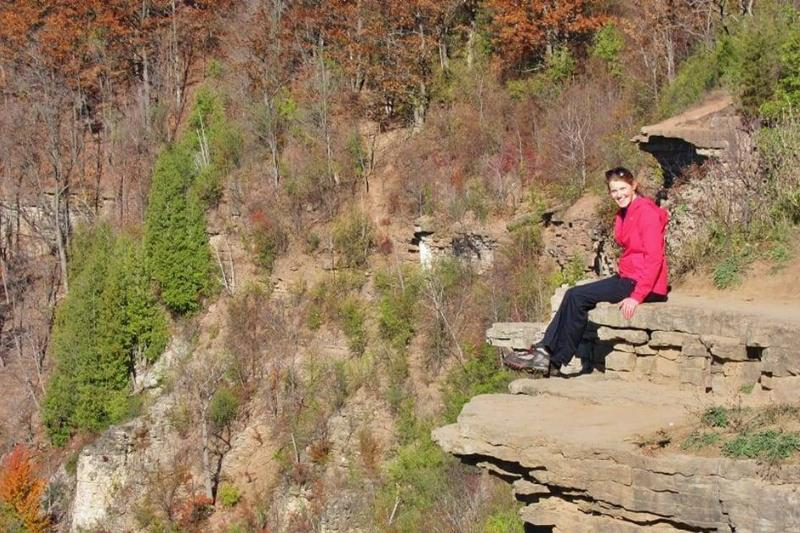 A woman sits on the cliff.