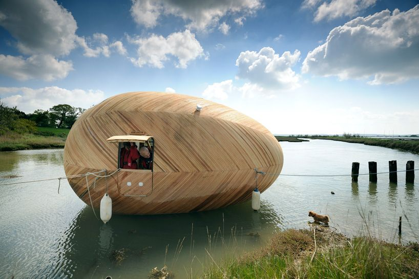 A man sails in a wooden egg boat.