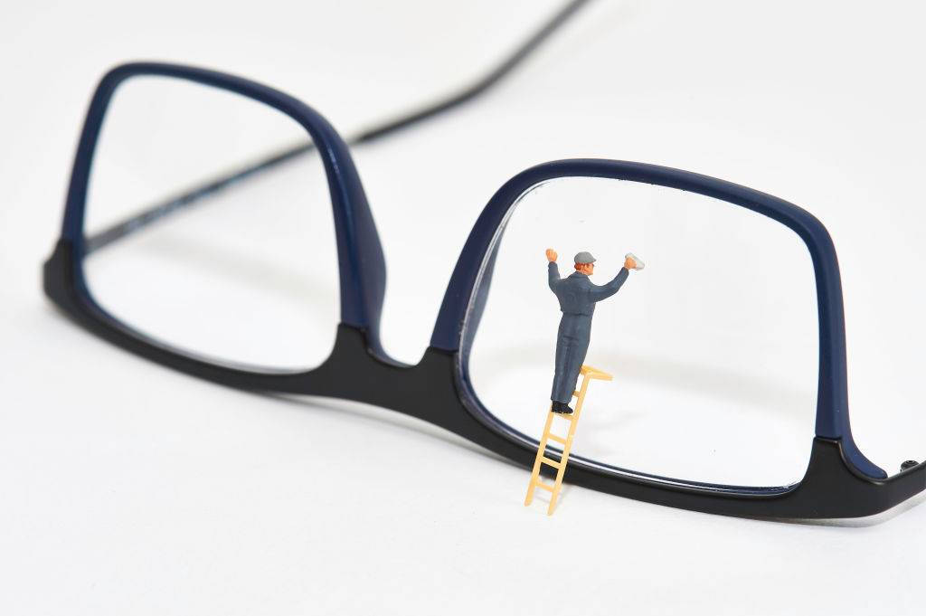 a figurine of a window cleaner next to a pair of blue and black glasses