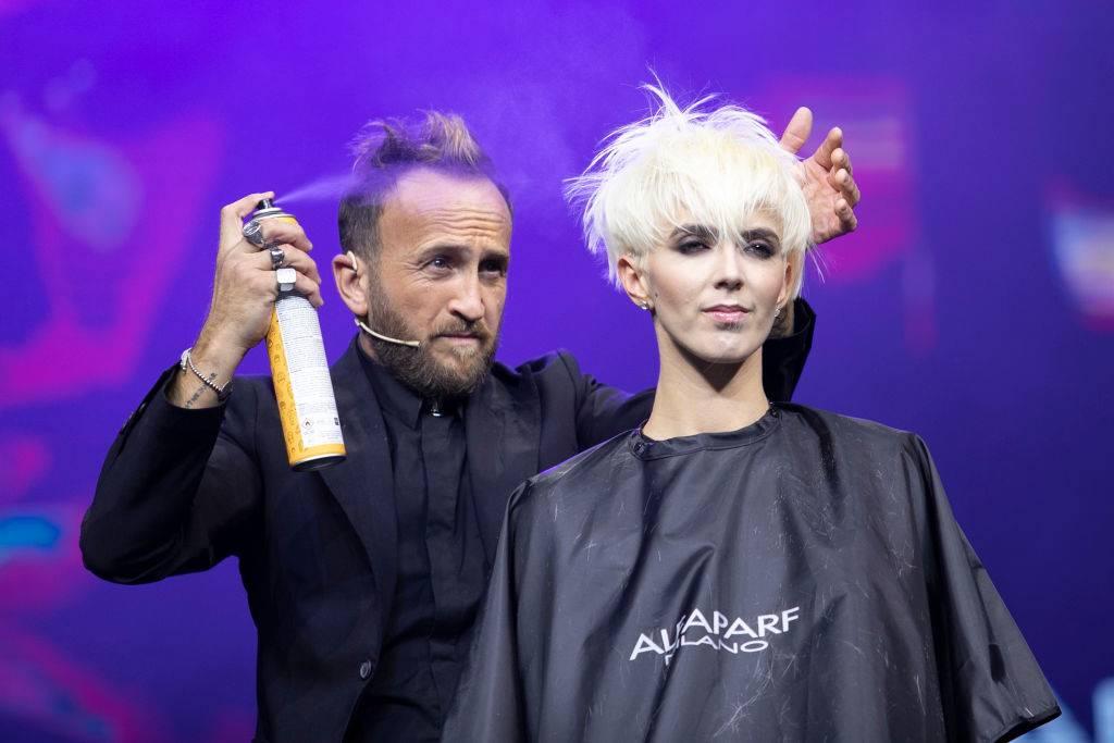 a man spraying hairspray on a woman's hair