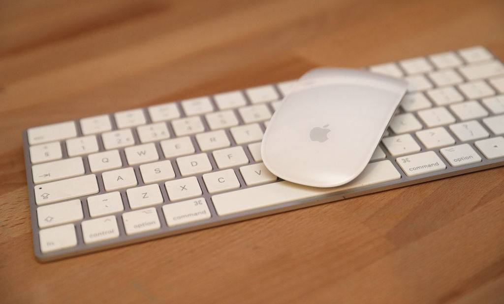 an apple keyboard and mouse on a wood desk