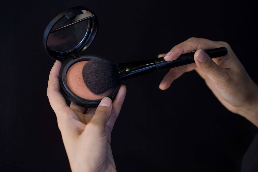 a makeup brush being dipped into blush