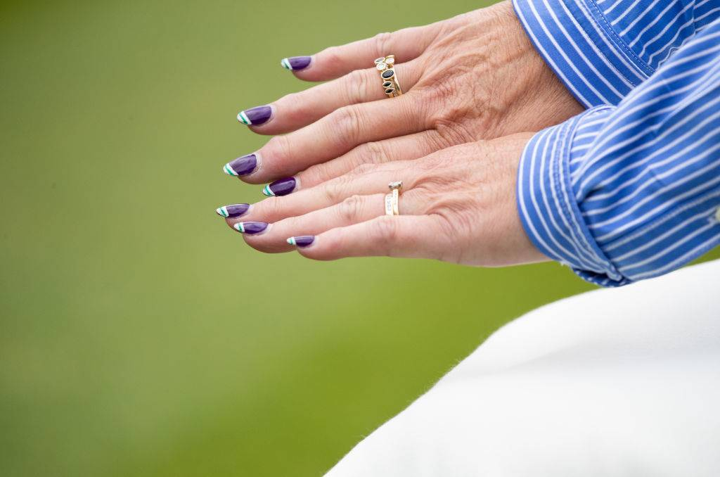 a woman with purple nail polish wearing rings