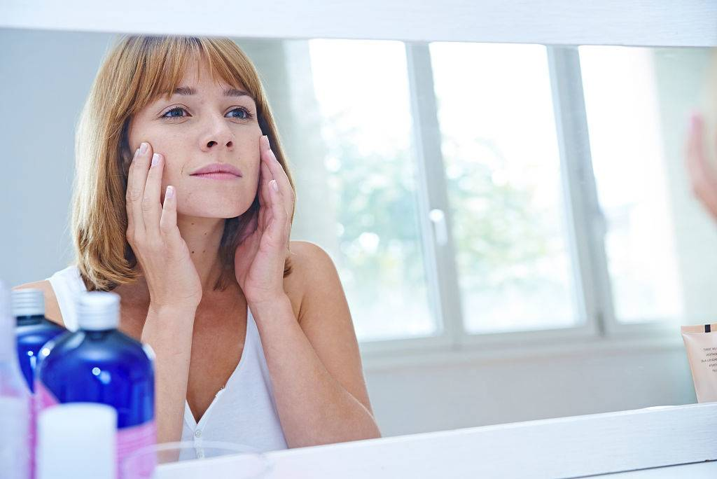 a woman looking in a mirror and touching her face