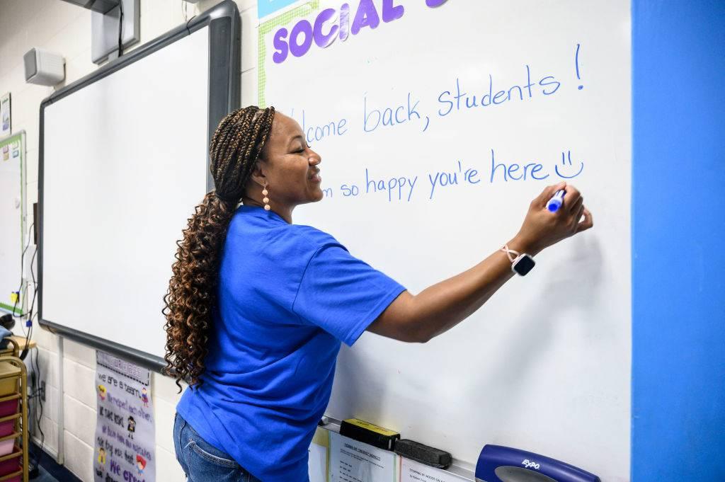 a teacher writing on a whiteboard
