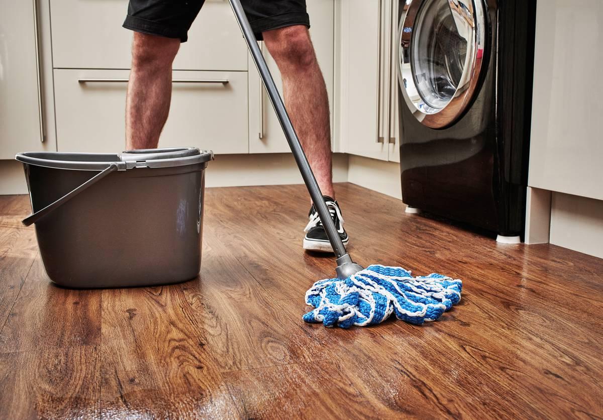 A man mops a wooden kitchen floor.