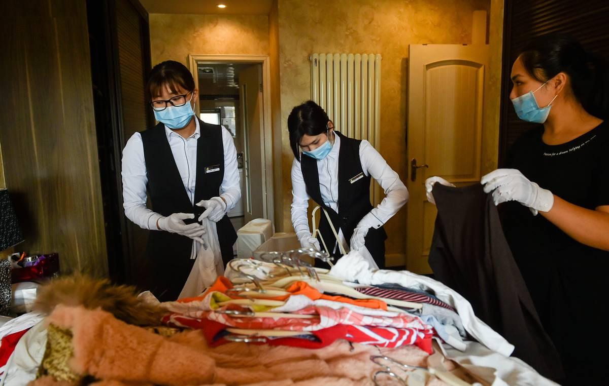 Wardrobe organizers sort through a client's clothes.