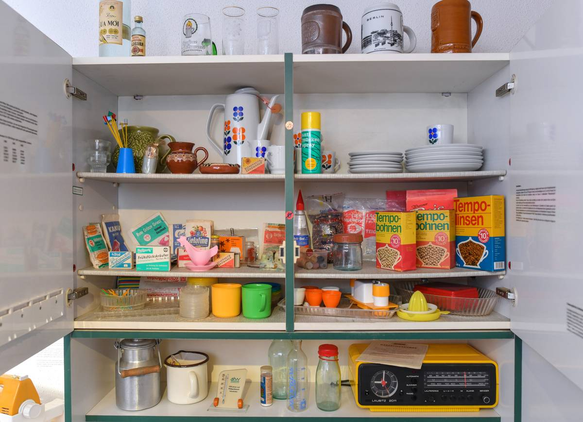 An open cupboard in a kitchen is full of food.
