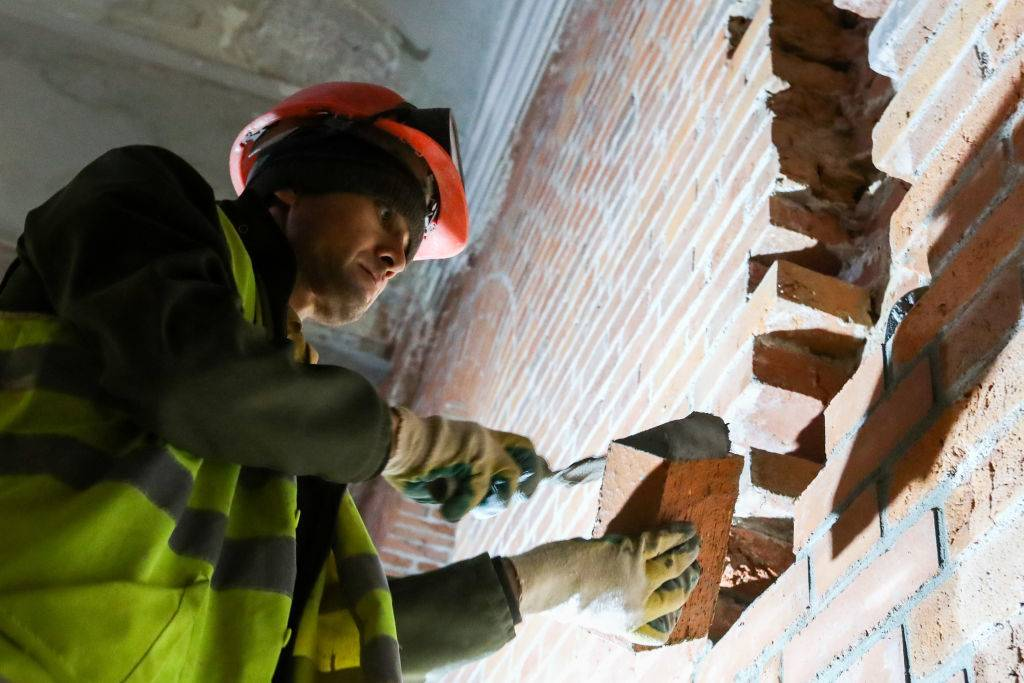 A construction worker stacks bricks.