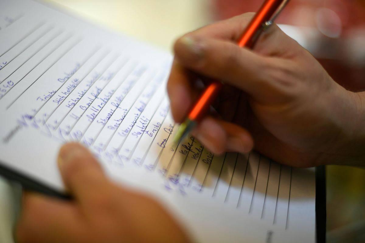 A man writes a shopping list.